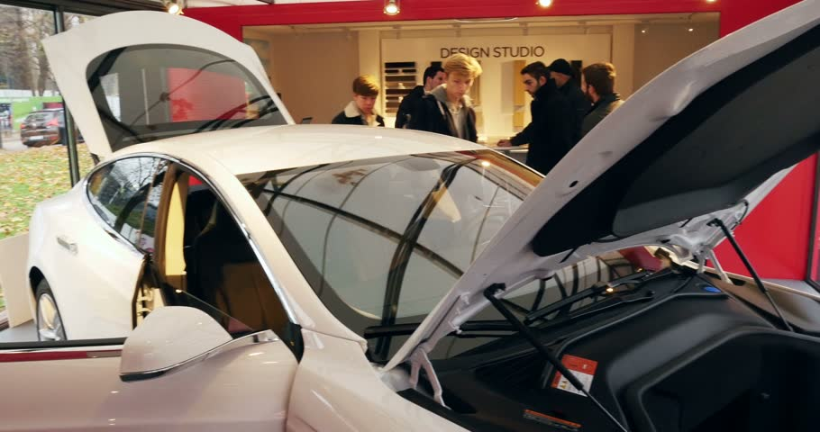 admirado : PARIS FRANCE  CIRCA 2015: Tesla Car being admired by customers inside Design Center showroom. Tesla is an American company that designs manufactures and sells electric cars Stock Footage