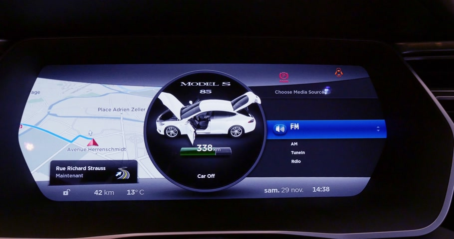 ekonomi : PARIS FRANCE  CIRCA 2015: Searching for radio station on the LCD dashboard screen on a touchscreen of a Tesla Model S luxury car. Tesla is an American company that designs manufactures and sells electric cars