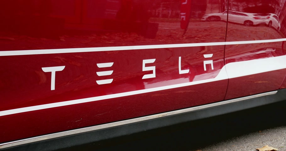 tesla model s : PARIS FRANCE  CIRCA 2015: Focusing to red Tesla Model S signage at  showroom. Tesla is an American company that designs manufactures and sells electric cars