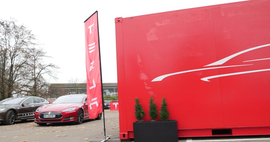 tesla model s : PARIS FRANCE  CIRCA 2015: Panning over Tesla showroom to the red and gray electric Tesla Modesl S cars. Tesla is an American company that designs manufactures and sells electric cars
