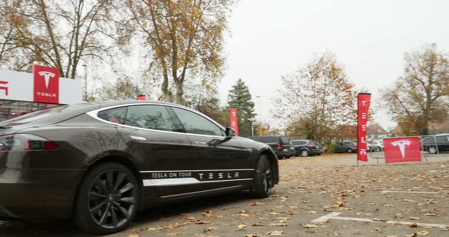 tesla model s : PARIS, FRANCE - CIRCA 2015: Left panning to dark gray Tesla Model S hybrid car in front of showroom. Tesla is an American company that designs, manufactures, and sells electric cars