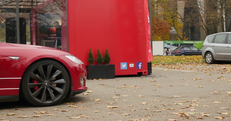 tesla model s : PARIS, FRANCE - CIRCA 2015: Left panning to Red Tesla Model S hybrid car in front of showroom. Tesla is an American company that designs, manufactures, and sells electric cars