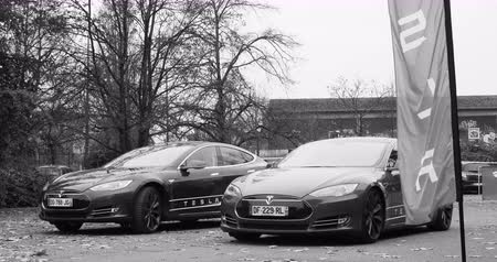 tesla model s : PARIS, FRANCE - CIRCA 2015: Two Tesla Hybrid in front of showroom - black and white. Tesla is an American company that designs, manufactures, and sells electric cars Stock Footage