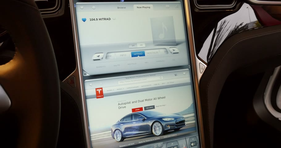 tesla model s : PARIS, FRANCE - CIRCA 2015: Large LCD dashboard screen monitor with touch-screen capabilities of a Tesla Model S luxury car. Tesla is an American company that designs, manufactures, and sells electric cars