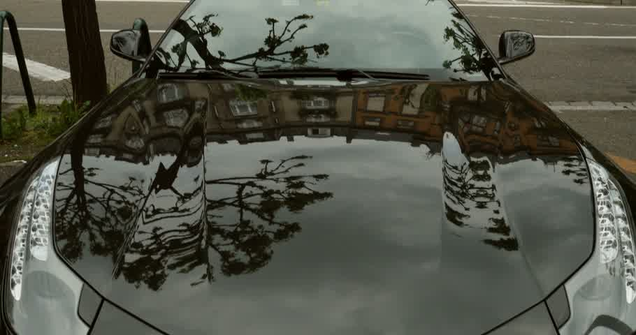 pininfarina : PARIS, FRANCE - CIRCA 2015: Tilt-down from building faade to black Ferrari FF model parked in city. The Ferrari FF - Ferrari Four is a four seats and four-wheel drive grand tourer and is the fastest four-seat automobile Stock Footage