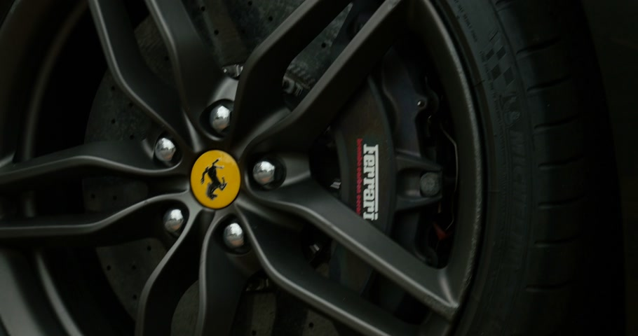 pininfarina : PARIS, FRANCE - CIRCA 2015: Panning to Ferrari wheel brake system with logotype on a Ferrari FF model. The Ferrari FF - Ferrari Four is a four seats and four-wheel drive grand tourer and is the fastest four-seat automobile Stock Footage