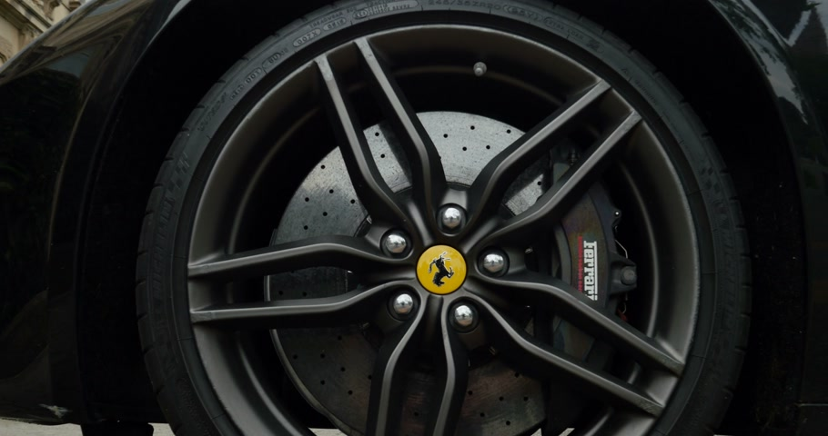 pininfarina : PARIS, FRANCE - CIRCA 2015: Zoom-in to Ferrari wheel brake system with logotype on a Ferrari FF model. The Ferrari FF - Ferrari Four is a four seats and four-wheel drive grand tourer and is the fastest four-seat automobile