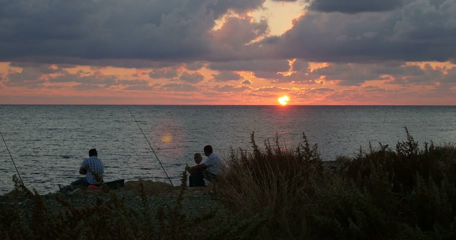 ciprus : Silhouettes of three men preparing their gear for fishing from rocks on the  Cyprus coast at sunset