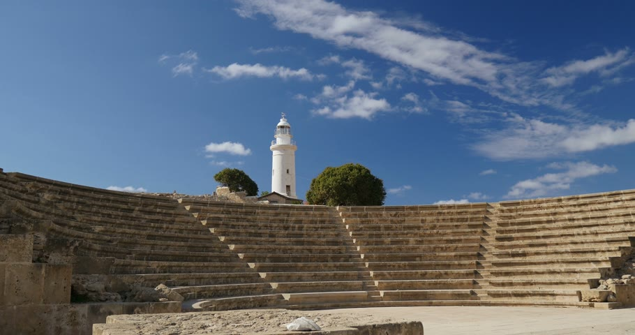 escada : Tilt down to white lighthouse behind Odeon  Amphitheatre Pano Odeon Paphos against blue sky of Cyprus on a clear summer day Stock Footage