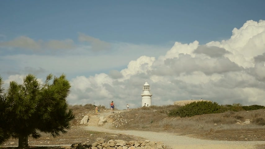 pont : Mother and three children walking towards lighthouse, slow motion - rear view Stock mozgókép