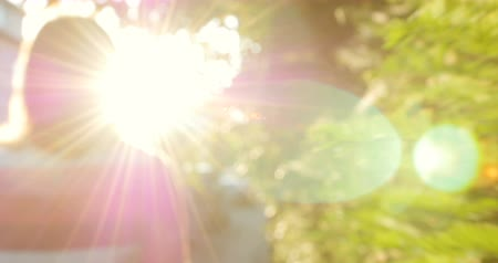 hipster : Woman walking towards sun on a summer warm calm street with beautiful lens flare Stock Footage