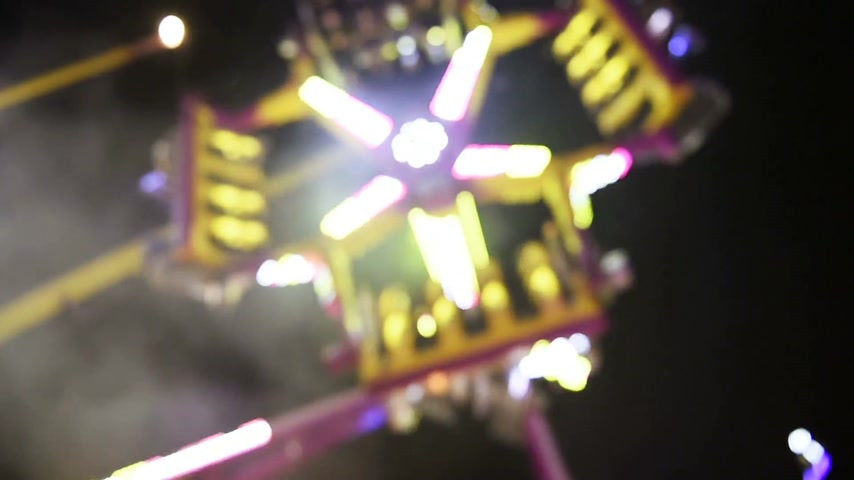 admirado : Defocused view of a ride  with large carousel in amusement theme park during a summer night admired by family
