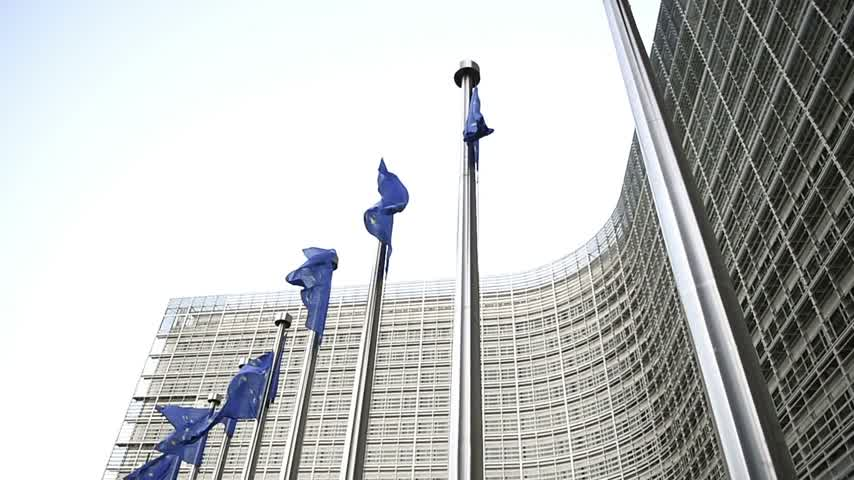 funcionários : Tilt-down to waving Flags of European Union in front of the office windows of the Berlaymont building of the European Commission in Brussels, Belgium