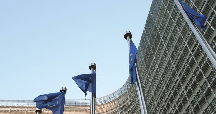 funcionários : Panning to waving Flags of European Union in front of the office windows of the Berlaymont building of the European Commission in Brussels, Belgium Stock Footage