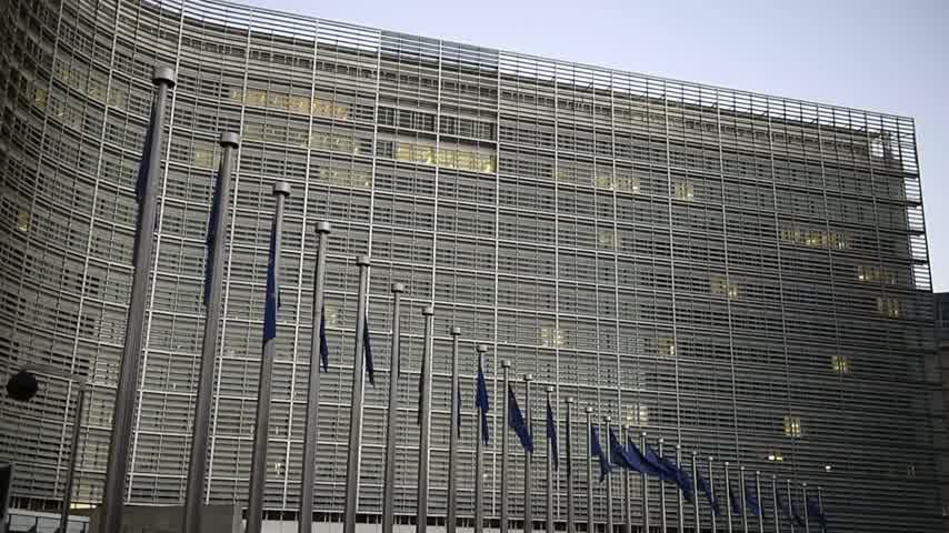 funcionários : Flags of European Union in front of the office windows of the Berlaymont building of the European Commission in Brussels, Belgium waving Stock Footage