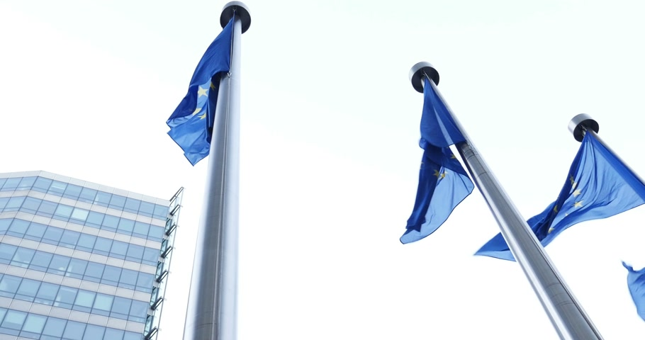 funcionários : Flags of European Union in front of the office windows of the Berlaymont building of the European Commission in Brussels, Belgium waving - seen from below