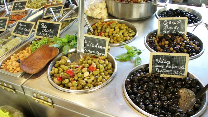 olive colored : Large variety of fresh olives and olive oil on rustic typical French market background