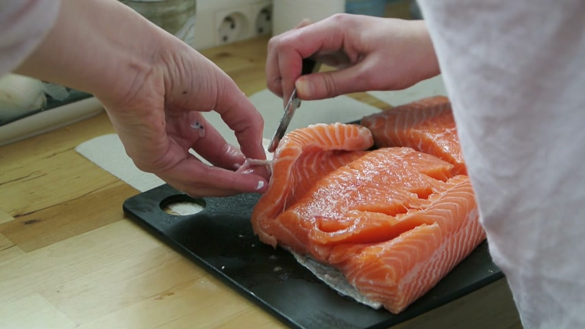 comida japonesa : Detailed view of woman peeling organic red salmon filet for food for gourmet food preparation