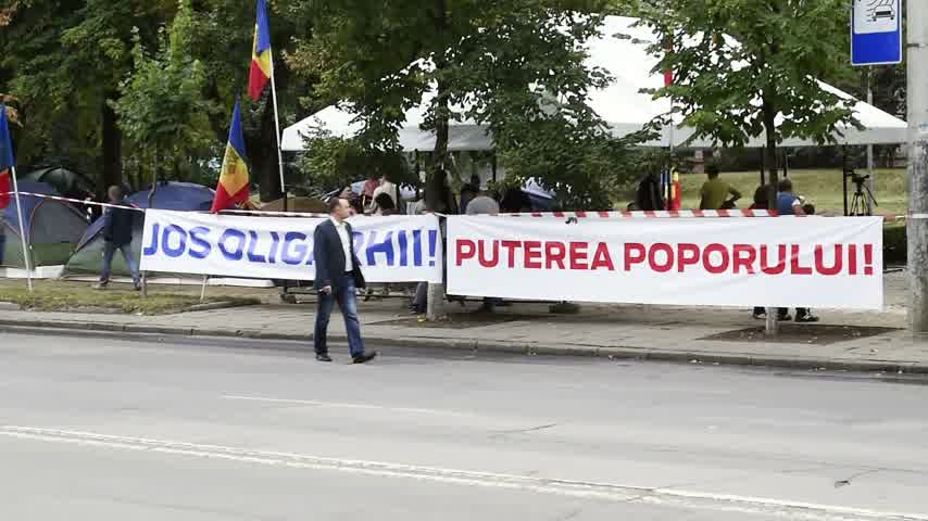 igor : CHISINAU, MOLDOVA - SEP 2015 Man inspecting protesters camp outside Parliament House of Moldova with anti oligarch banner. They seek the dismissal of officials after the 1 bn euro went missing Stock Footage
