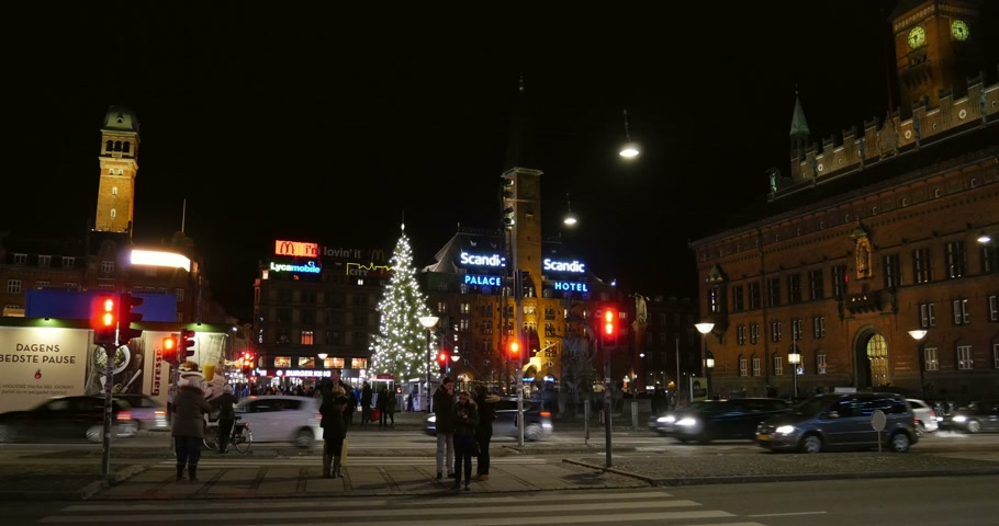 kodaň : COPENHAGEN, DENMARK - CIRCA 2015: People waiting to pass the street in front of Copenhagen City Hall Kobenhavns Radhus on a snowy night with Christmas Tree and snow cleaner tractor
