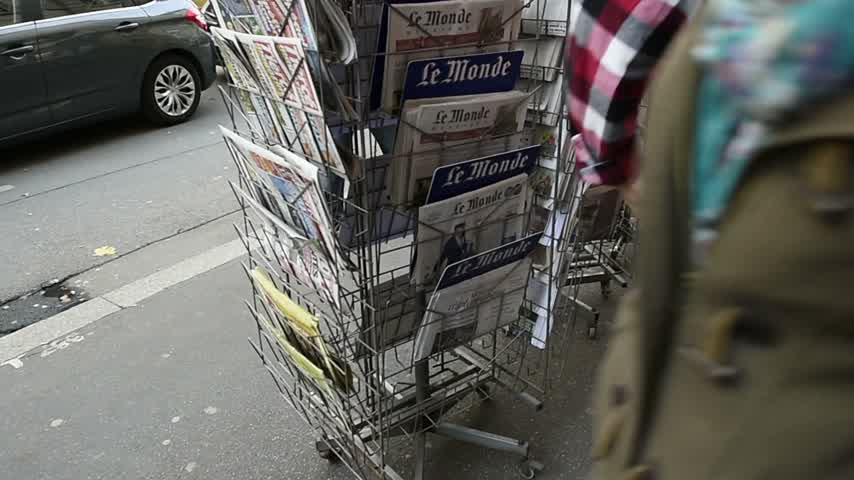 je suis charlie : STRASBOURG, FRANCE - 14 NOV, 2015: Couple reading front covers at press kiosk of International newspapers display headlining the terrorist attacks  in Paris