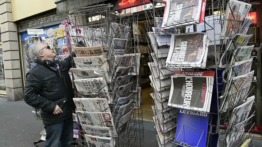 mobilization : STRASBOURG, FRANCE - 14 NOV, 2015: Man buying reading front covers at press kiosk of International newspapers display headlining the terrorist attacks  in Paris