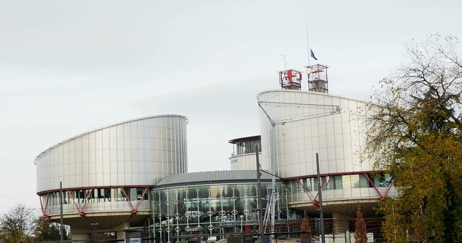 je suis charlie : STRASBOURG, FRANCE - 14 Nov 2015: European Union Flag flies at half-mast in front of the European Court of human Rights following an terrorist attack in Paris Stock Footage
