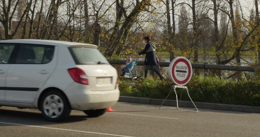 mobilization : STRASBOURG, FRANCE - NOV 14 2015: French Police checking vehicles on the Bridge of Europe between Strasbourg and Kehl Germany, as a security measure in the wake of attacks in Paris - slow down police sign
