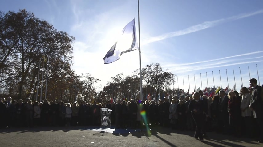 flag half mast : STRASBOURG, FRANCE - NOV 16, 2015: Council of Europe employees after the minute of silence in tribute to the victims of the attacks in Paris which left at least 129 people dead
