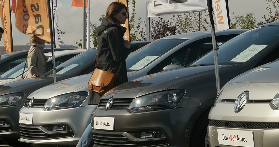 clientes : STRASBOURG, FRANCE - CIRCA 2015:   Woman walking between rows of Volkswagen cars and choosing the right Volkswagen after the Volkswagen Gate - Volkswagen emission scandal Vídeos