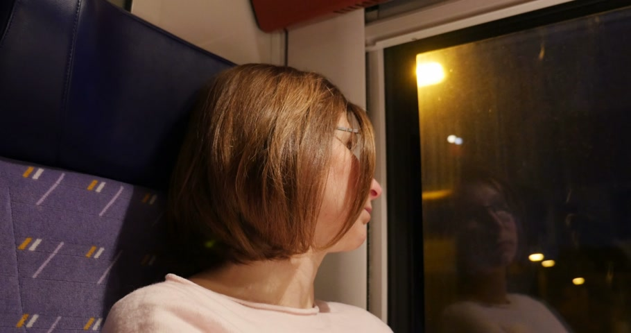 vacation destination : Sad melancholic woman travel alone in night train admiring the landscape from the other side of the window