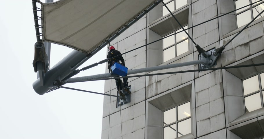 arche : PARIS, FRANCE - CIRCA 2015: Window cleaning worker hanging with ropes and swinging on the high floor of La Defense, Grande Arche, Paris shot with a telephoto lens zoom. Stock Footage