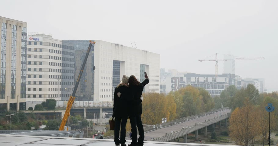 self portrait photography : PARIS, FRANCE - CIRCA 2015: Two friends taking paired selfies and laughing after sharing photo in La Defense Business district, under La Grande Arche, Paris, Ile-de-France, France Stock Footage