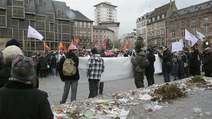 protestor : STRASBOURG, FRANCE - JAN 30, 2016: Protesters gathered at Kleber Square Place Kleber during a demonstration, protesting governments plan of the extension of the state of emergency for another three months - Justice and Freedom placard