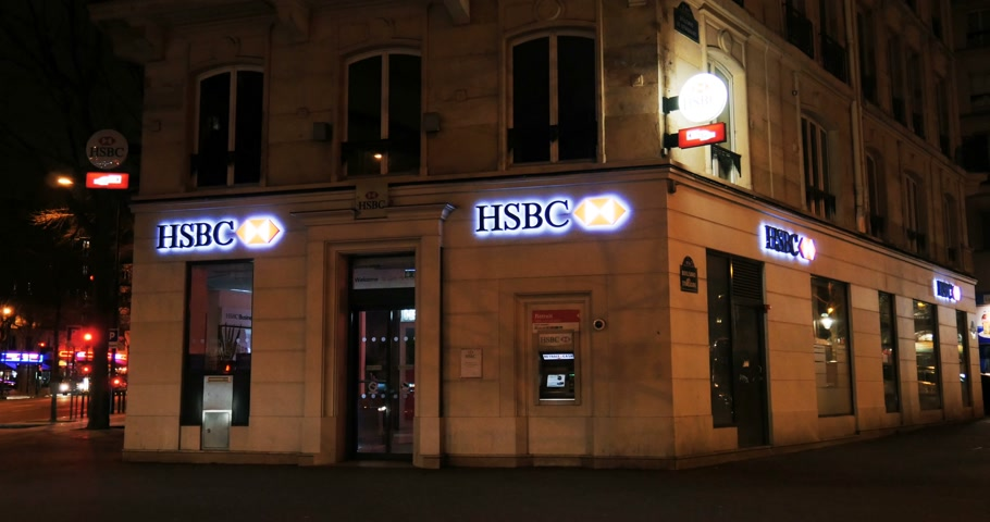 bancos : PARIS, FRANCE - CIRCA 2016: Hong Kong and Shanghai Banking Corporation Limited or HSBC bank branch headquarter in Paris, France at night Stock Footage