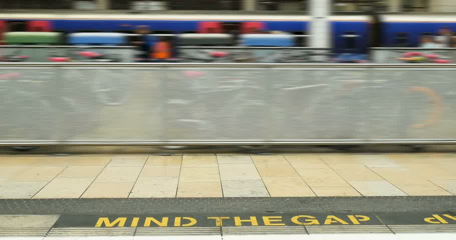 mind the gap : Mind The Gap iconic sign at train station tube in London, United Kingdom with defocused people in the background Stock Footage