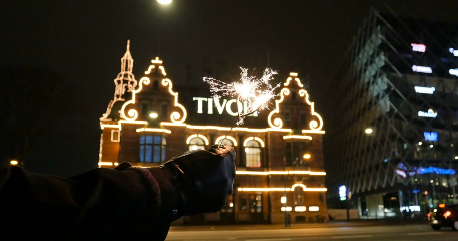 kodaň : COPENHAGEN, DENMARK - CIRCA 2016: Woman holding sparkle with heart shape against the illumination main building of Tivoli Amusement Park in central Copenhagen Dostupné videozáznamy