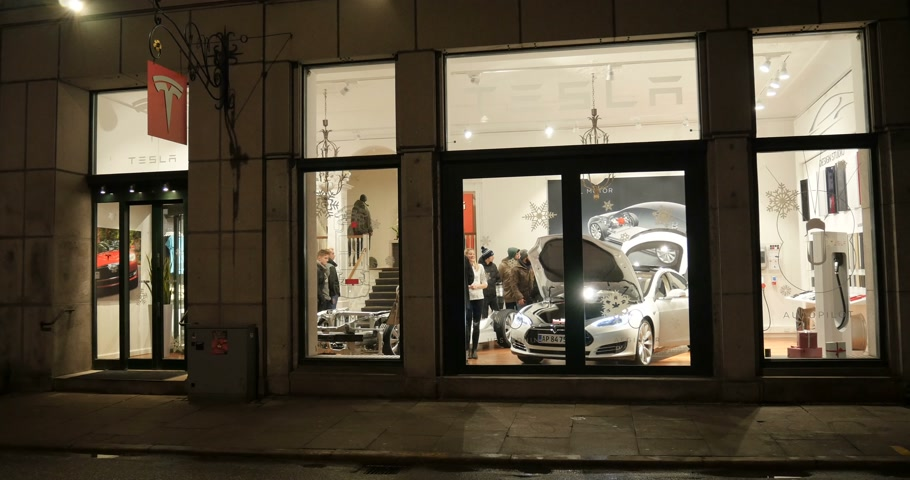 model s : COPENHAGEN, DENMARK - CIRCA 2016: New Tesla Motors showroom in central Copenhagen with customers visiting the showroom. Tesla is an American company that designs, manufactures, and sells electric cars