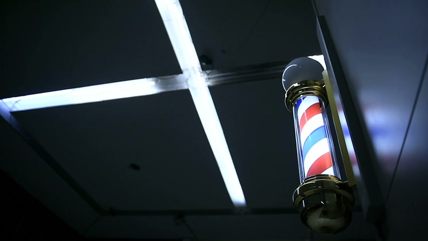 kadeřník : Americana - rotating illuminated barber shop sign on street at night
