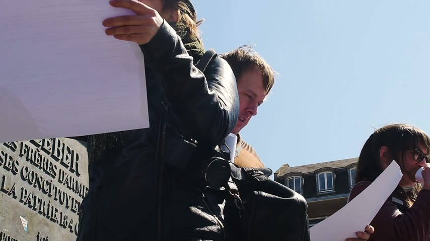 improvised : STRASBOURG, FRANCE - APR 20, 2016: Woman speaking in improvised megaphone as hundreds of people demonstrate as part of nationwide day of protest against proposed labor reforms by Socialist Government Stock Footage