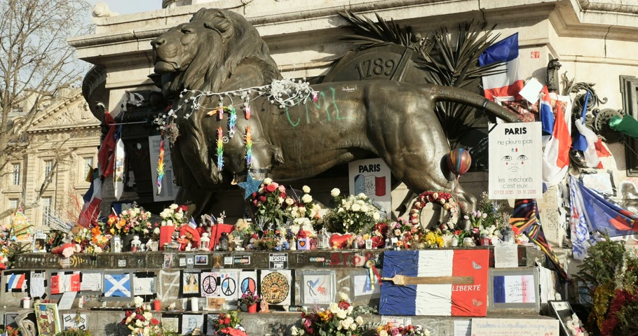 je suis charlie : PARIS, FRANCE - CIRCA 2015: Lion statue at the Monument a la Republique surrounded with placards and signs and flags after Paris attacks at Bataclan Theater