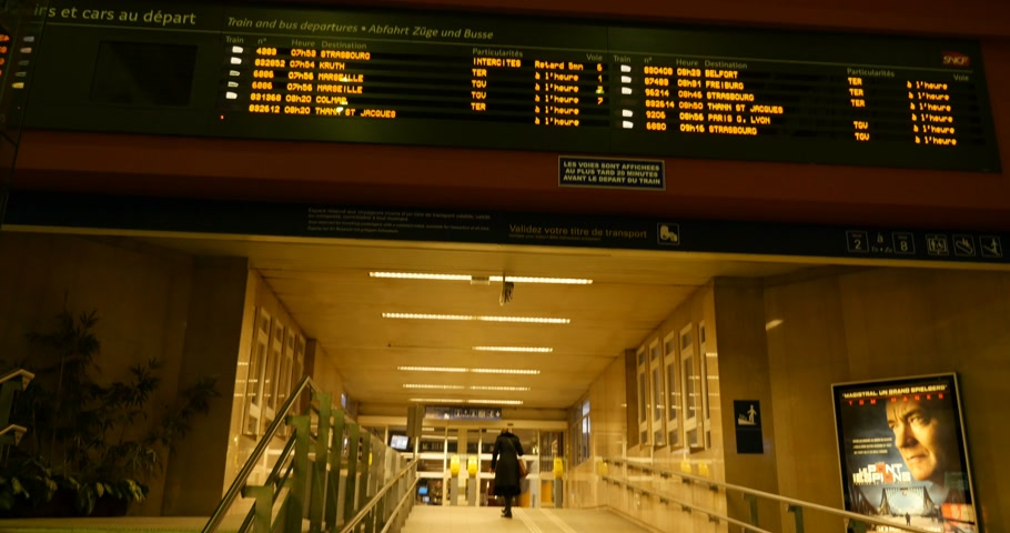 chegada : MULHOUSE, FRANCE - CIRCA 2016: Train information, arrival and departure board at French train station with one woman preparing to leave the train station area to embark on a train Vídeos