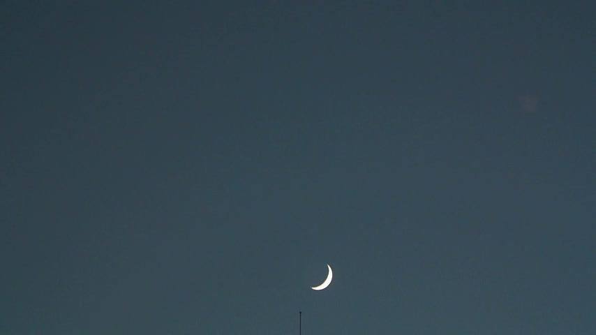 telescopic : Beautiful lighthouse with super moon behind as seen in twilight - filmed with super long telescopic lens