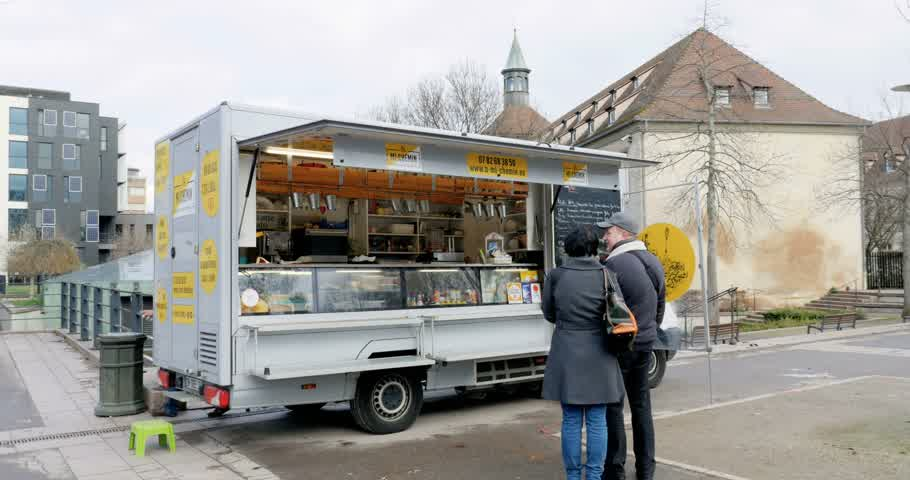 meal : STRASBOURG, FRANCE - CIRCA 2016: Couple deciding what to buy from a mobile vintage food truck Stock Footage