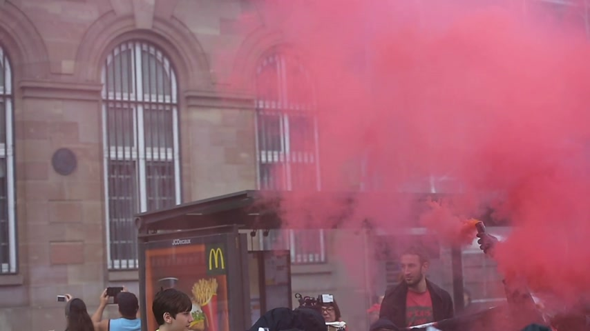 protestor : STRASBOURG, FRANCE - MAY 19, 2016: Group with covered faces and smoke grenades throwing paint towards Banque de France building during a demonstrations against proposed French governments labor and employment law reform Stock Footage