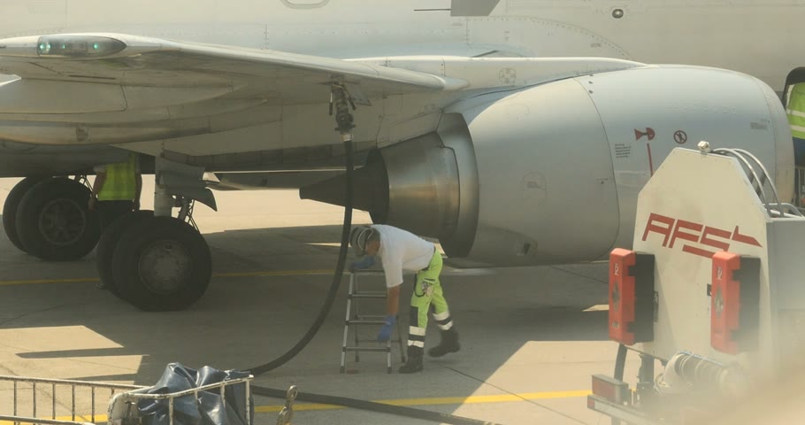 ar : FRANKFURT, GERMANY - CIRCA 2016: Airport service engineer charge the hose inserted into the wing of the aircraft to refuel passenger airplane