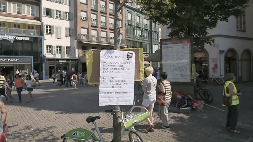 af : STRASBOURG, FRANCE - AUG 22 2015:People protest in against immigration policy and border management which asks for commitment in the wake of migrants boat disasters - man protesting with placards and flag Stok Video
