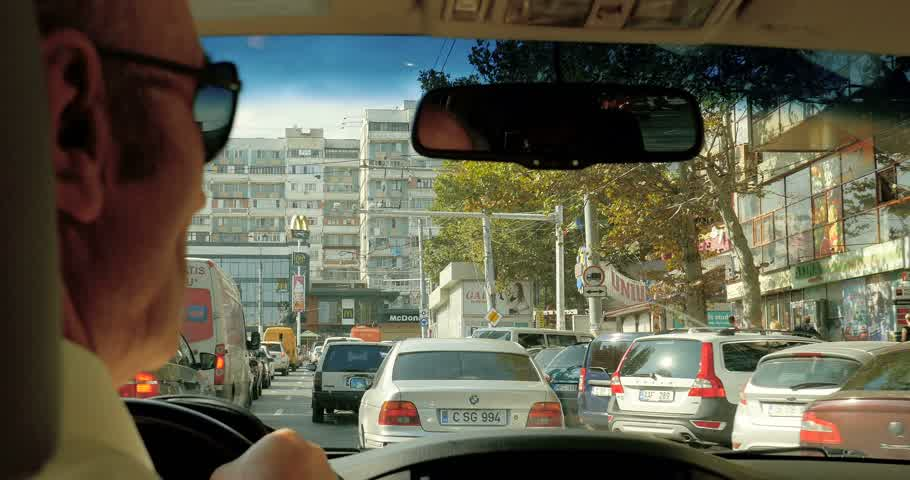 preso : CHISINAU, MOLDOVA - CIRCA 2016: Senior man driving SUV car in the center of Chisinau with heavy traffic jam and communist architecture building in the foreground