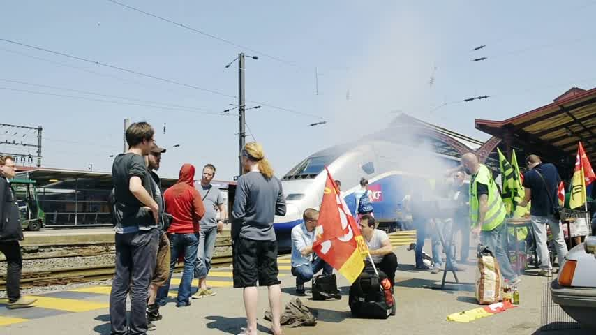 protestor : STRASBOURG, FRANCE - JUN 6, 2016: Peaceful protesters making barbeque outside the Gare de Strasbourg, during a demonstration by railway workers of French state rail operator SNCF, as part of a strike to defend their work conditions.