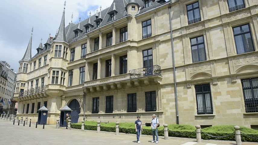 saray : LUXEMBOURG, LUXEMBOURG - CIRCA 2016: Father and son taking photo in front of the Grand Ducal Palace in Luxembourg.  It is the official residence of the Grand Duke of Luxembourg, and where he performs most of his duties as head of state of the Grand Duchy. Stok Video